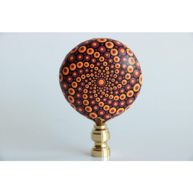 Pair of lamp finials crafted from hand-painted stones featuring a colorful, spotted pattern in fall colors, mounted on a...