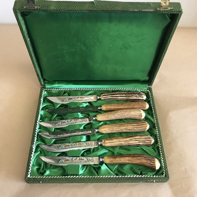 Set of six antler handle steak knives by Anton Wingen Jr. These German Rostfrei steak knives feature a wildlife scene on...
