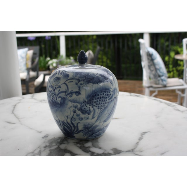 This vintage blue and white decorative porcelain ginger jar comes with a lid and depicts a pair of Asian Goldfish...