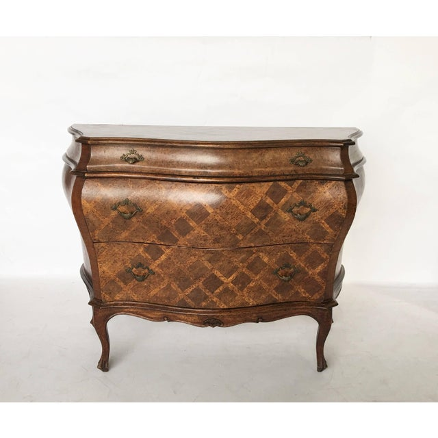 A Rococo style three-drawer Italian bombe commode or chest of drawers with inlaid cross hatch design, sitting on cabriole...
