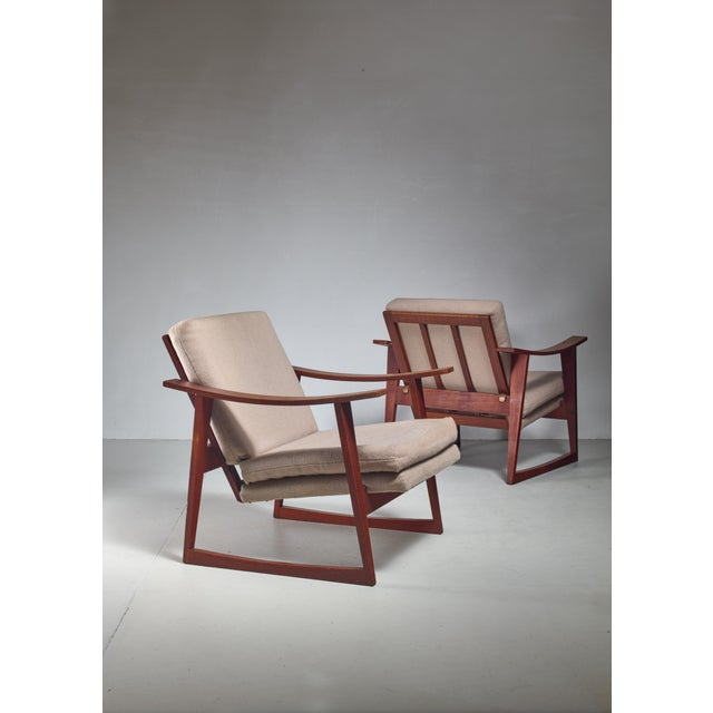 A pair of Danish teak lounge chairs, in the manner of Hans Wegner. The chairs have loose grey fabric cushions.