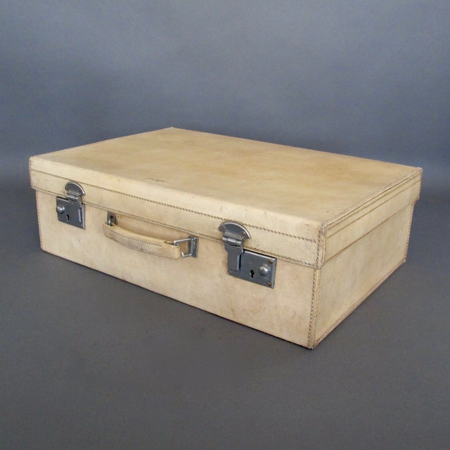 Elegant classic cream vellum suitcase from England. The case is made from sturdy pigskin, has a solid pigskin handle and...