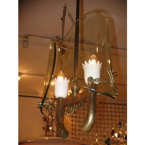 Fontana Arte chandelier featuring a body in brass with two light sources, white lacquered bulb holders and two clear...