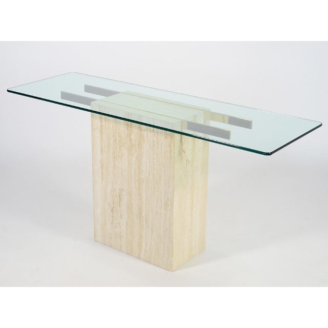 An elegant minimalist form, this console table by Ello has a base of Italian travertine marble and a pair of brass arms...