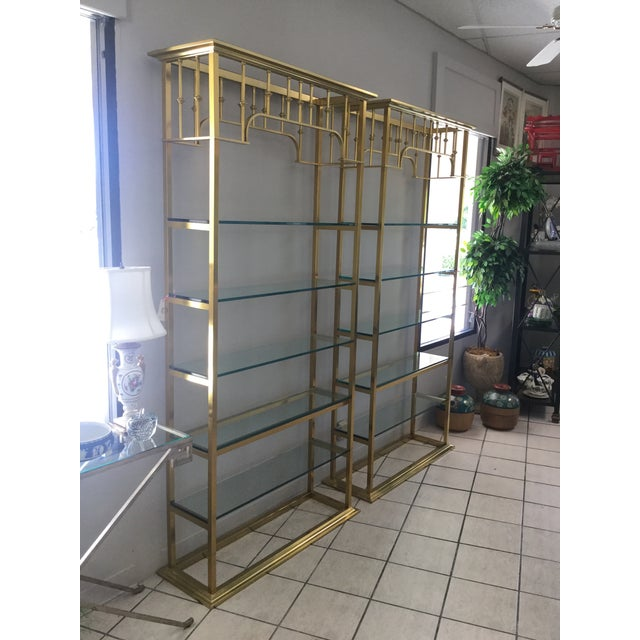 Vintage 2 brass etageres complete with glass shelves. Made in the 1970's in the style of art deco.