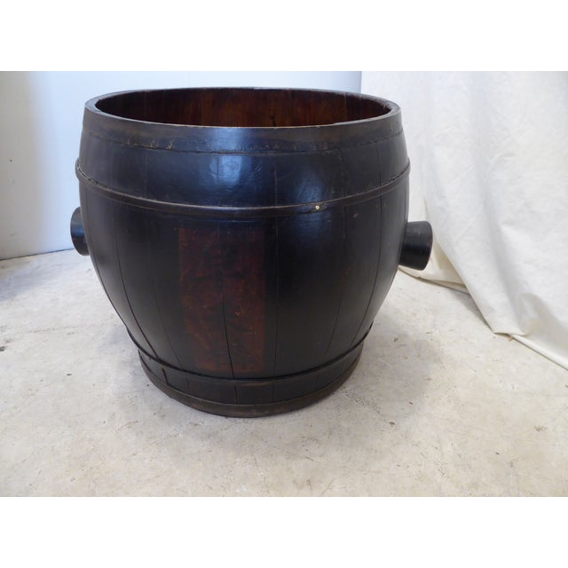 Japanese laquered barrel with red labels on both sides, brass bound, with handles.