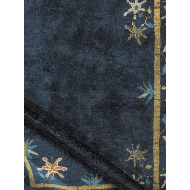 A wonderful example of a Chinese Art Deco style rug woven circa 1920 with a plain navy ground encircled by flowers and...