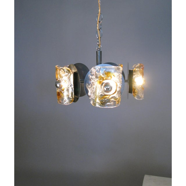 A beautiful vintage 1960s hanging chandelier light fixture with a chrome frame and five lights with curved hand blown...