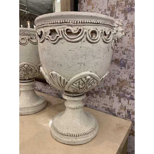 Beautiful large pair of white ceramic urns from Italy. In excellent condition! The detail is amazing on them.