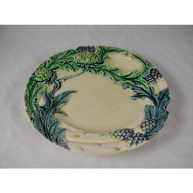 A French Majolica plate made by Fives-Lille, Circa 1890. This piece is for serving both Artichokes or Asparagus and shows...