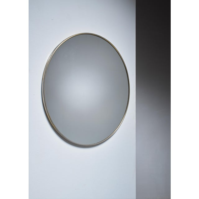 A large and round wall mirror in a brass frame. Simplicity and elegance with beautiful mildly aged brass.