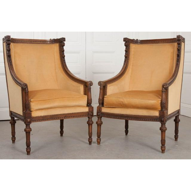 A fabulous pair of hand-carved, Louis XVI style bergères, made in France during the 19th century. The upholstered pair...