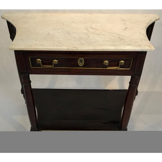 Beautiful mahogany console table having white marble top, bottom wooden shelf and single drawer. The decorative gold...