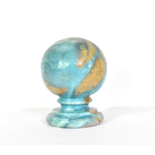 A vintage Italian paperweight in blue and tan carved and polished alabaster, round, with a pedestal. By Duccheschi, made...