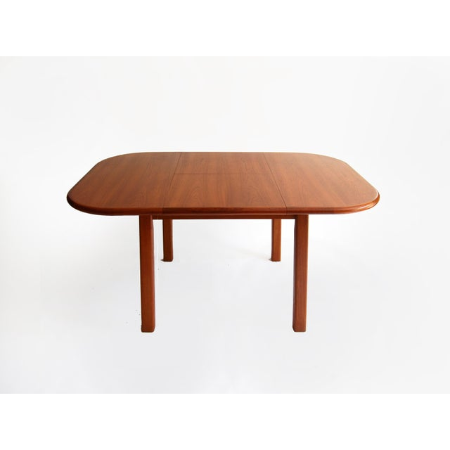 Scandinavian style extending dining table by D-Scan. The table has a square shape top with rounded corners and a hidden...