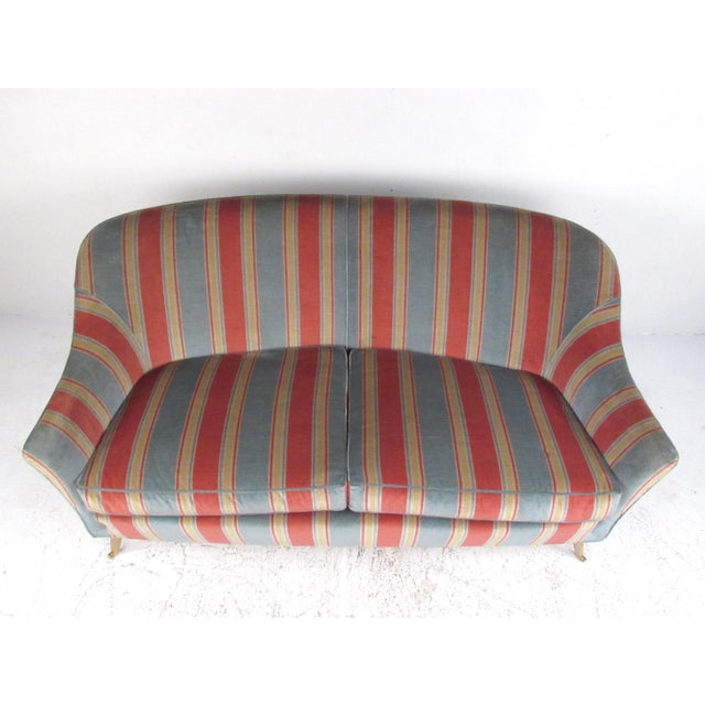 This stunning Italian modern sofa features Gio Ponti style, lovely vintage fabric, tapered brass legs, and comfortable...