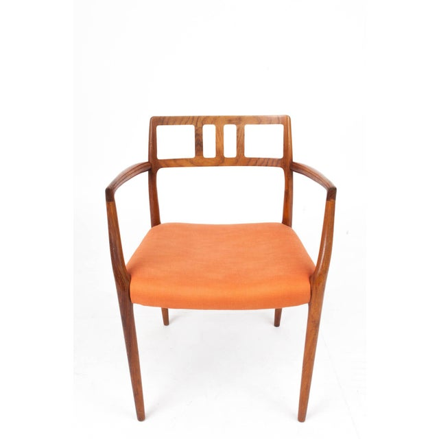 Elegant Scandinavian Modern side chair by Niels Otto Møller with sinuous arms, tapered legs, and a comfortable, delicately...