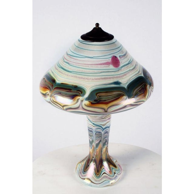A craftsman table lamp with a colorful pulled feather design over opal-white ground glass shade and body, signed to the...