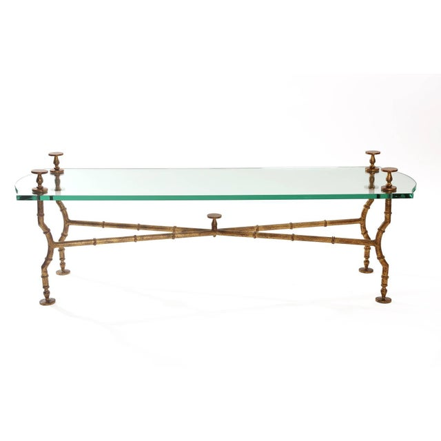 Stunning gold leafed steel and glass cocktail table after Maison Baguès and Giacometti. This all original example has...