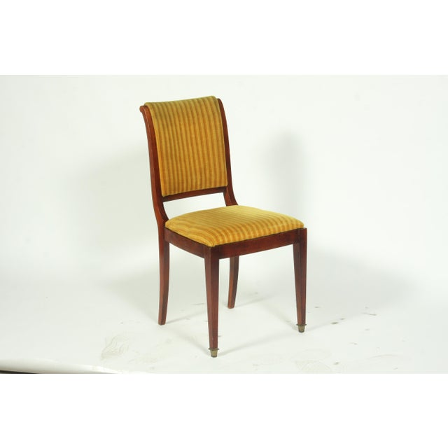 Set of French Regency-Style dining room chairs featuring, gold velvet striped upholstery, mahogany sabre' legs with brass...