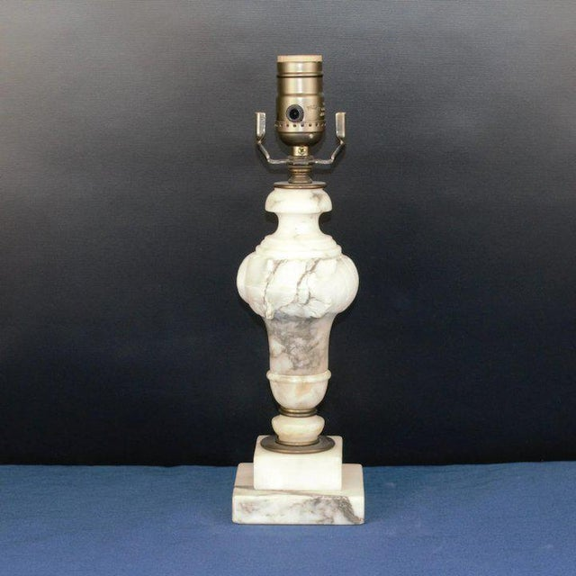 A beautiful deeply hand carved off white alabaster table lamp with grey veining. The oil rub bronze fittings are newer....