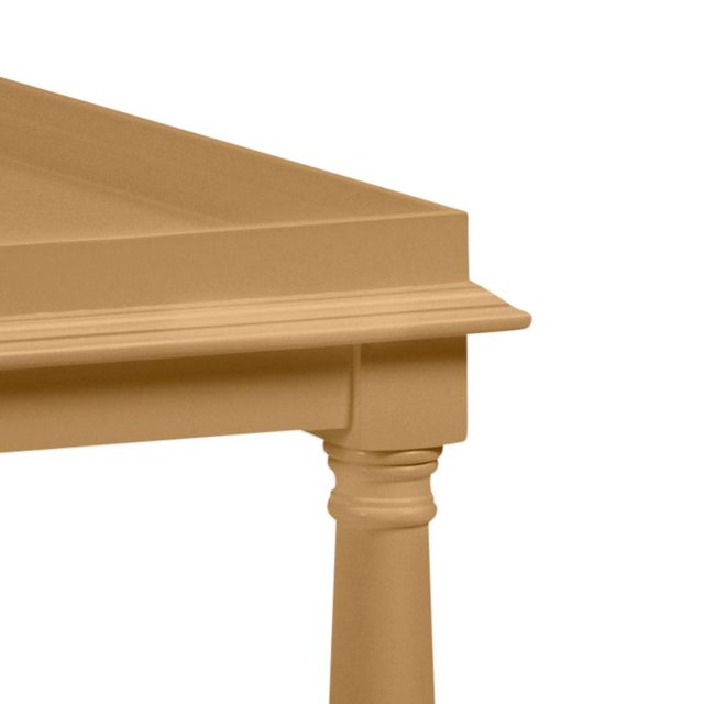 Made of acacia wood, this cocktail table features a gallery shelf and turned legs. Finish is Benjamin Moore Mystic Gold.