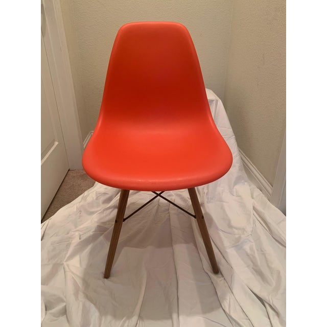 An authentic Eames molded plastic dowel leg side chairs in orange and walnut. These chairs were made in 2013 and are in...