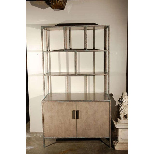 Paul Marra Bookcase shown in metal frame wrapped with embossed faux bronze, inset shelves and doors shown in gray wash....