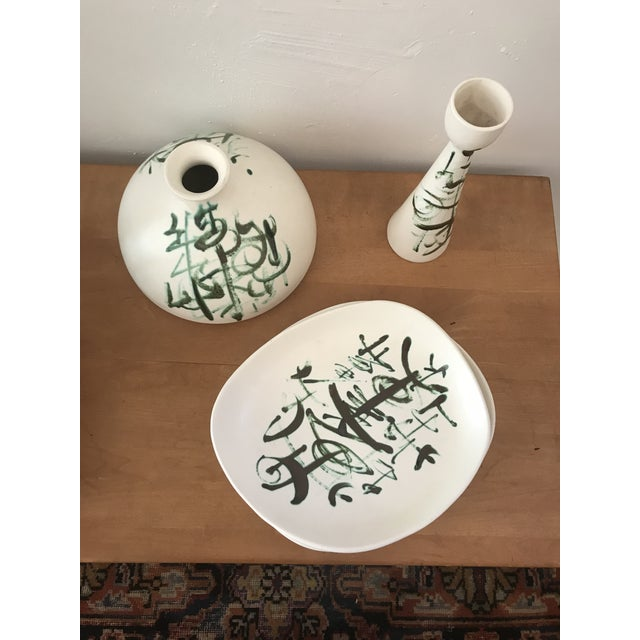 A striking white ceramic set of two plates, vase and a candelabra designed by Sascha Brastoff with green calligraphy like...