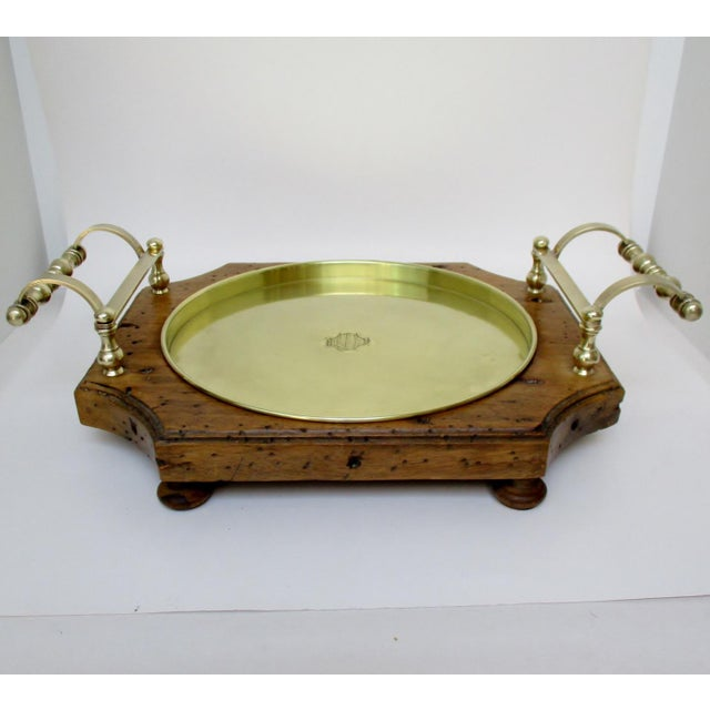 Rustic footed serving tray of made from aged wood with applied extended arced brass handles and brass tray. Tray measures...