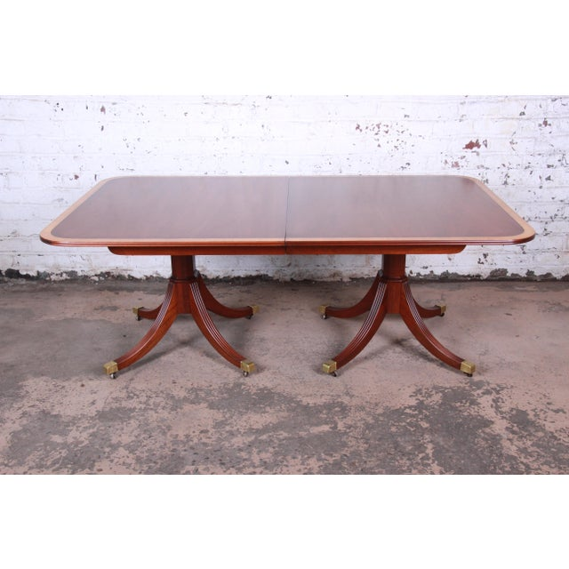 An exceptional banded mahogany double pedestal extension dining table by Kindel Furniture. The table features gorgeous...