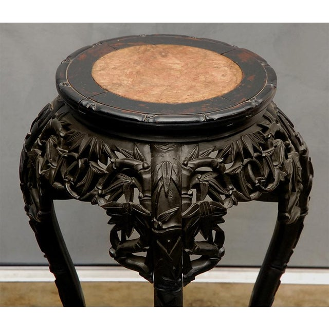 A nice oriental stand, circa 1900, probably Chinese, having a carved and ebony finish with a marble inset top. The pierced...