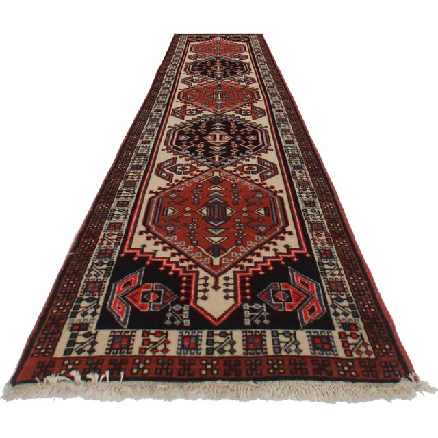 For sale is this vintage Persian Ardebil runner rug. Made of hand-knotted wool. Features funky geometric emblems.