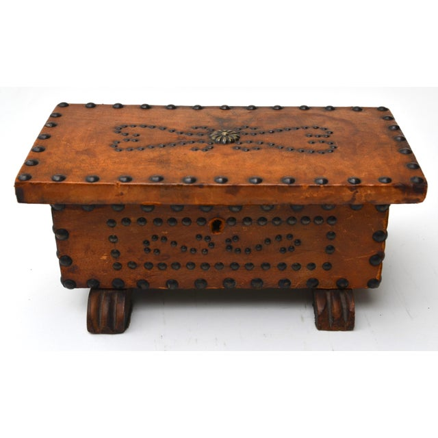 A leather clad box embellished with brass nail-heads and carved feet. Late 1800s to early 1900s. Bought in the 70s at a...