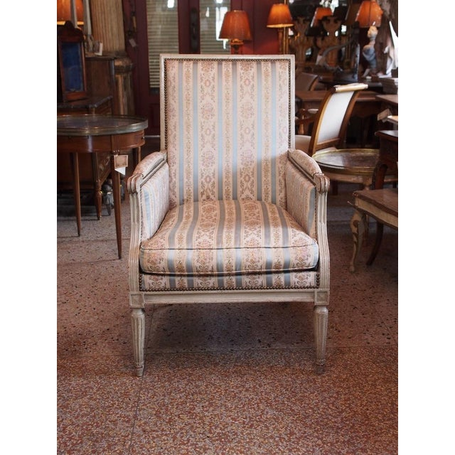 A gray/green painted Louis XVI bergere. Square back, upholstered arms, raised on tapering fluted legs. Classic upholstery...