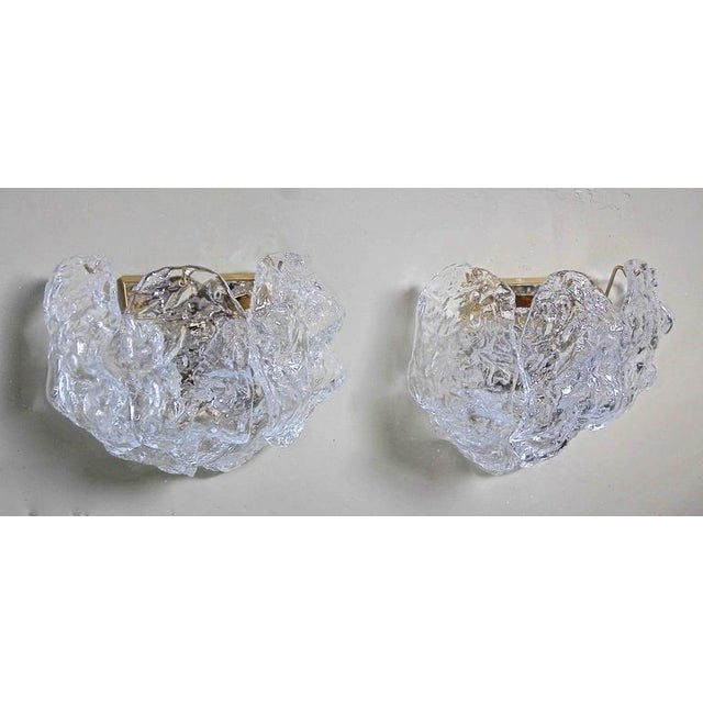Pair of Italian Murano handblown glass wall sconces with sculpted clear textured panels on brass-plated backplates. Each...