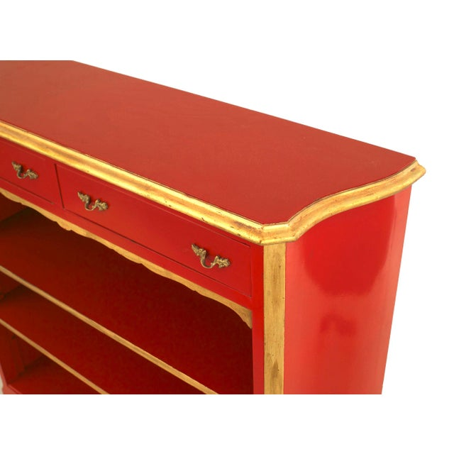 French 1940s (Louis XV style) red lacquered and gilt trimmed bookcase with two drawers above three shelves with a shaped...