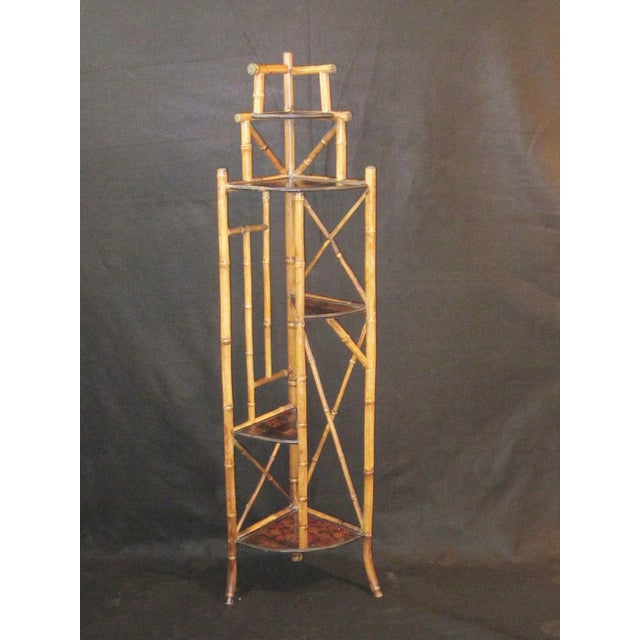 This is an antique Art nouveau corner etagere in bamboo with chinoiserie decoration on the surface of each shelf. It is...
