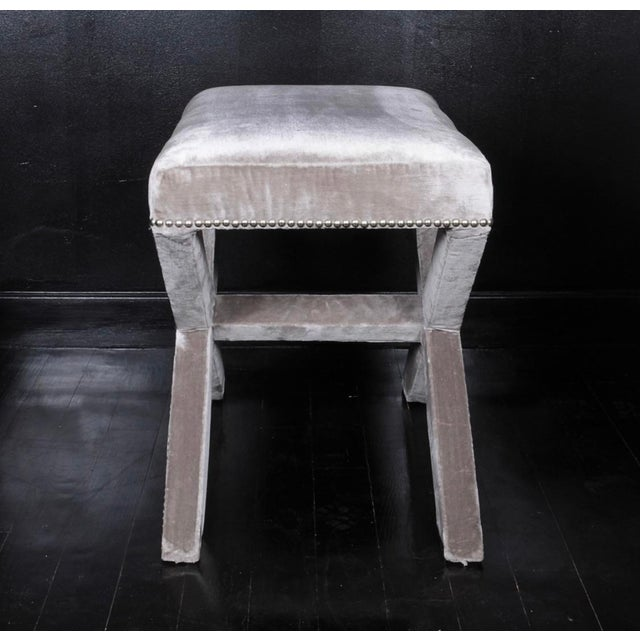 X-base stools upholstered in grey silk velvet with platinum nail heads. Sold as a pair.