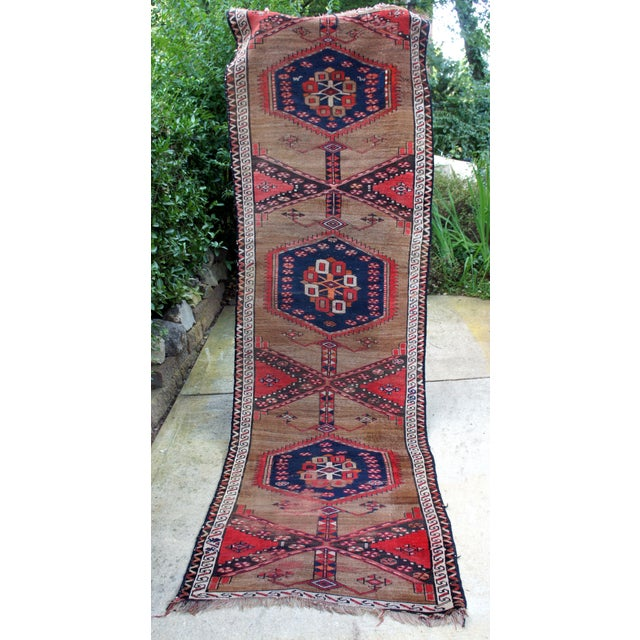 Antique Turkish Anatolian Kirshehir tribal runner rug featuring cerulean blue repeat medallions against an ochre field....