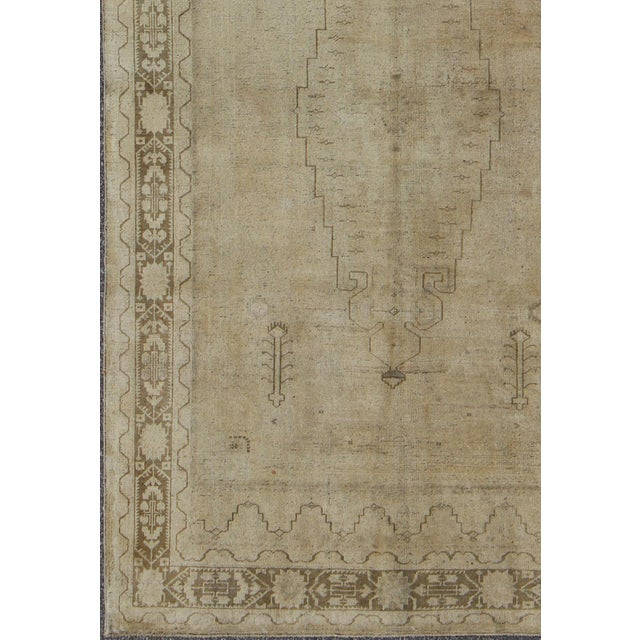 This faded vintage Turkish Oushak carpet (circa mid-20th century) features a central medallion design, as well as patterns...