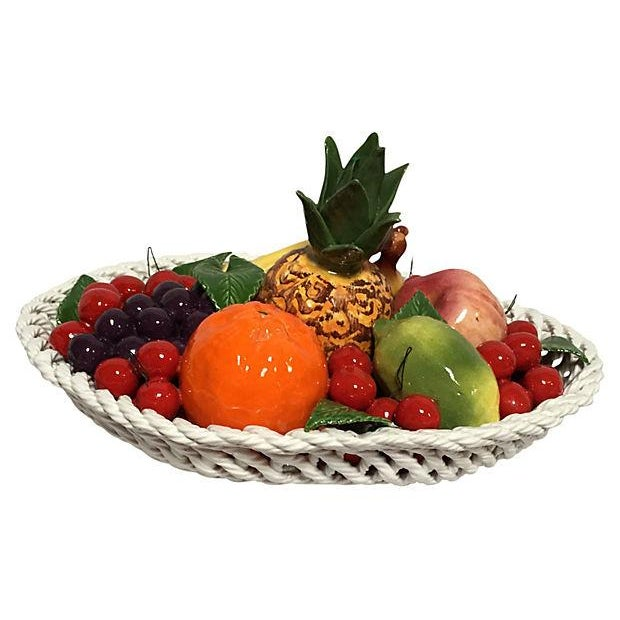 Large ceramic fruit bowl with cherries, grapes, an orange, a lime, pineapple, an apple, and banana bunch artfully...