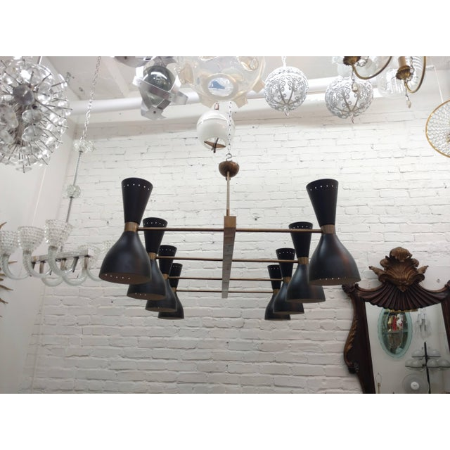 Large made to order contemporary fixture composed of ten satin black enameled shades. Each fitted with a set of candelabra...