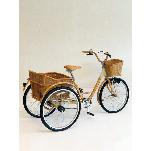 A cool 1980s steel frame tricycle wrapped with wicker and bamboo. The tricycle has a small wicker basket in the front and...