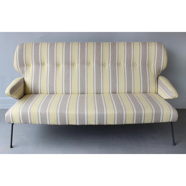 A mid-century Italian high wingback sofa settee in recent striped cotton material, with enameled metal legs, attributed to...