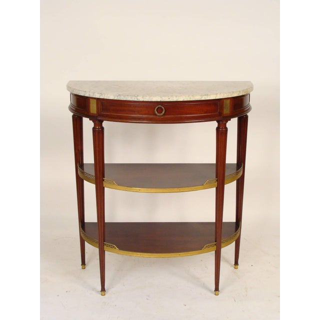Louis XVI style mahogany brass-mounted marble-top console table, in the style of Maison Jansen, circa 1930.
