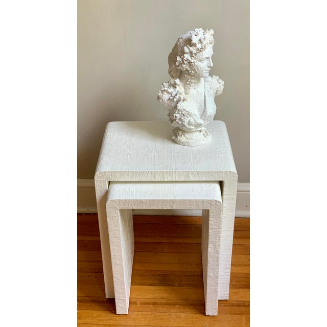 Beautiful pair of white grasscloth covered and painted nesting tables. Lacquered for durability and a glossy smooth...
