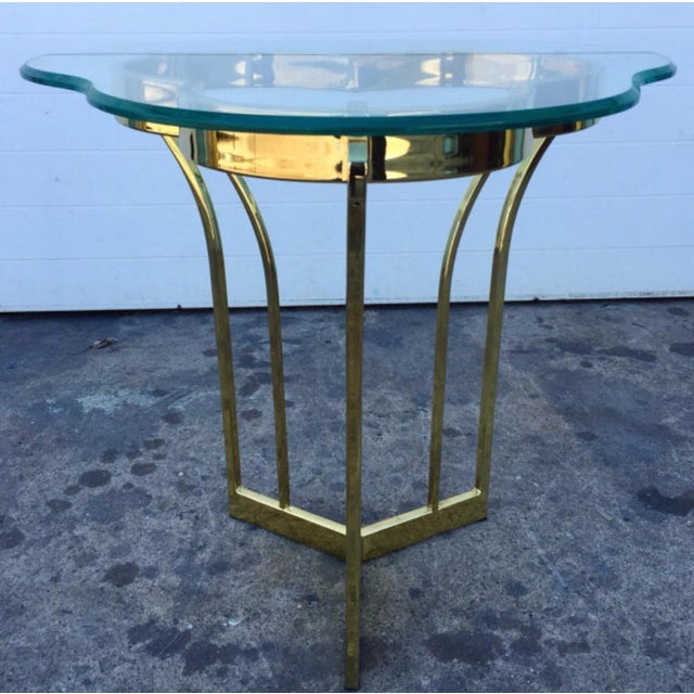 Tripartite form gold tone metal based table with glass top. Condition-very good vintage condition with minor signs of wear...