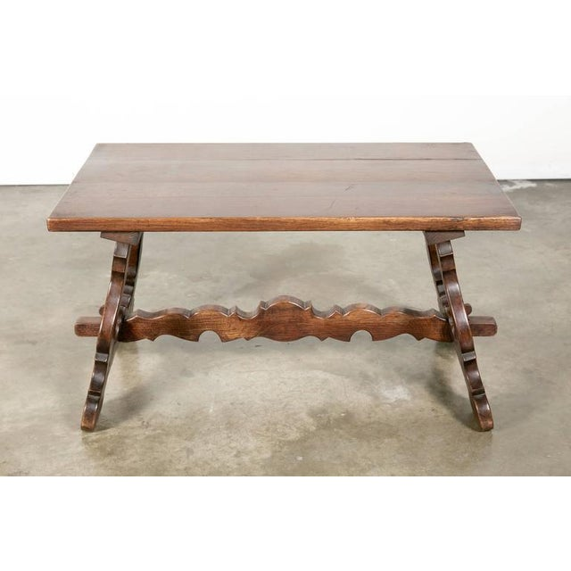 """A charming Spanish Colonial style coffee table constructed of solid oak. Graceful sculpted """"S"""" form legs joined by a..."""