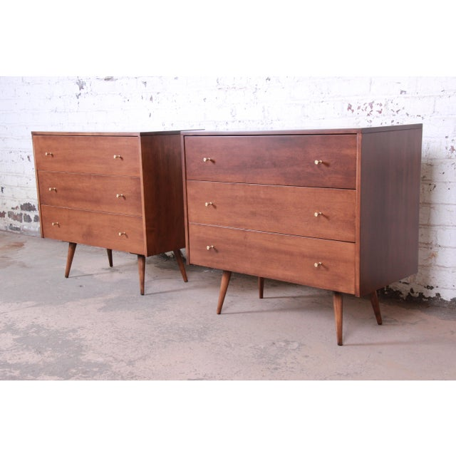 A stunning pair of mid-century modern three-drawer bachelor chests or bedside tables designed by Paul McCobb for his...